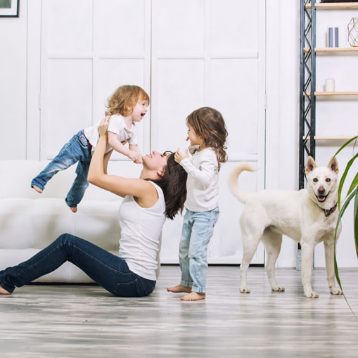 Photo of a woman sitting on a wooden floor, playing with two children and a white dog